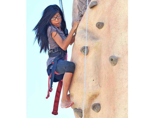 Bella Alcazar, 11, scales the rock-climbing wall at the Celebrating YOUth Sports Festival at the Santa Clarita Sports Complex on Saturday.