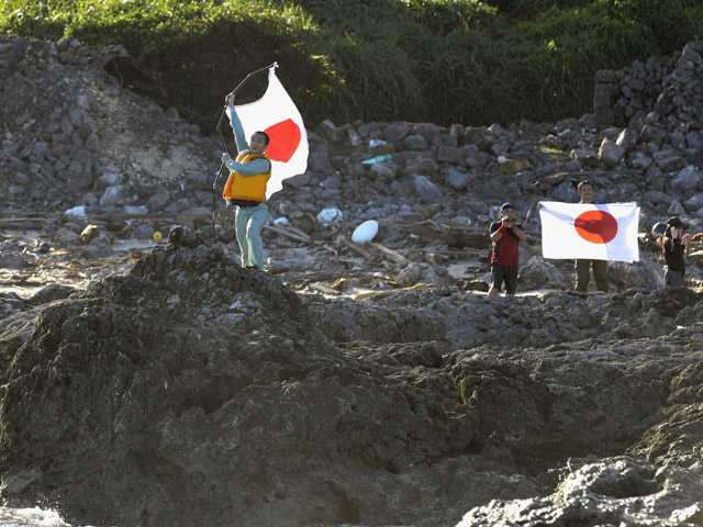 Japanese activists hold the national flags on Uotsuri island, one of the islands of Senkaku in Japanese and Diaoyu in Chinese, in East China Sea on Sunday.