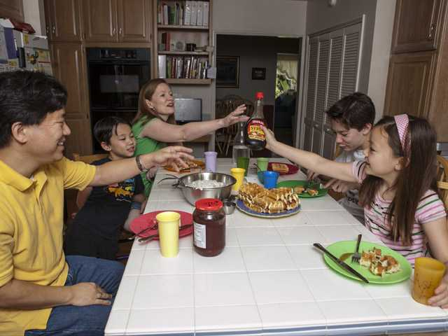 In this photo taken Tuesday, David Oh, a flight director of NASA's latest Mars mission, far left and his family have breakfast at 3 pm at their home in La Canada Flintridge.