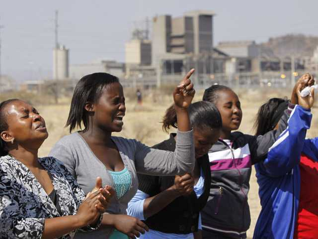 Women from a group of churchgoers wail at the site, Sunday  at the Lonmin platinum mine, background, near Rustenburg, South Africa, during a memorial service for 34 dead striking miners who were shot and killed by police last Thursday.