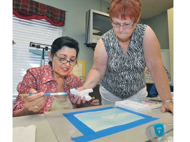 Class instructor Peggy Patti, right, demonstrates a technique for making clouds as student Mona Antchagno paints a watercolor sky and horizon at the SCV Senior Center recently.