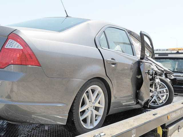 The damage on a Ford Fusion involved in a crash with a big rig is seen as it is towed away from southbound Interstate 5 at Lyons Avenue on Monday.