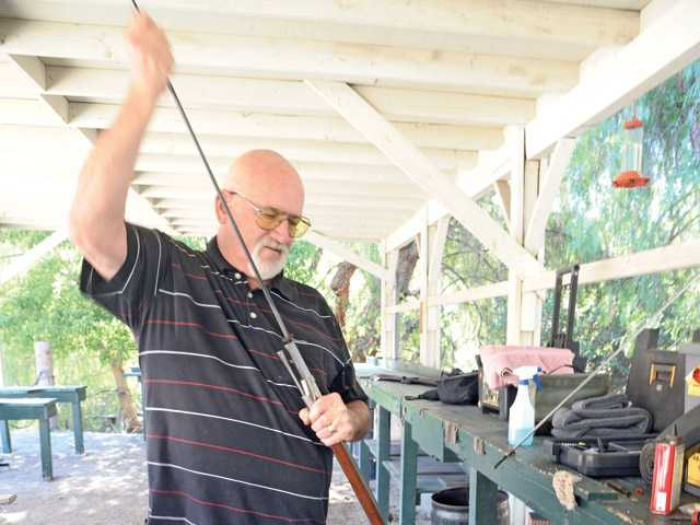 Kent Burton rams a .69-caliber lead ball down the barrel of his muzzle-loading musket.