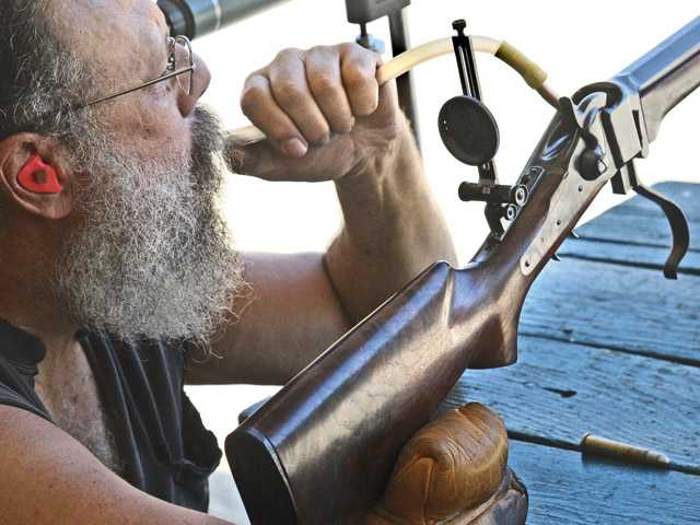 Burbank Muzzle Loaders member Ted Costello blows into his rifle to improve accuracy at Wes Thompson's Piru Gun Range on Wednesday.