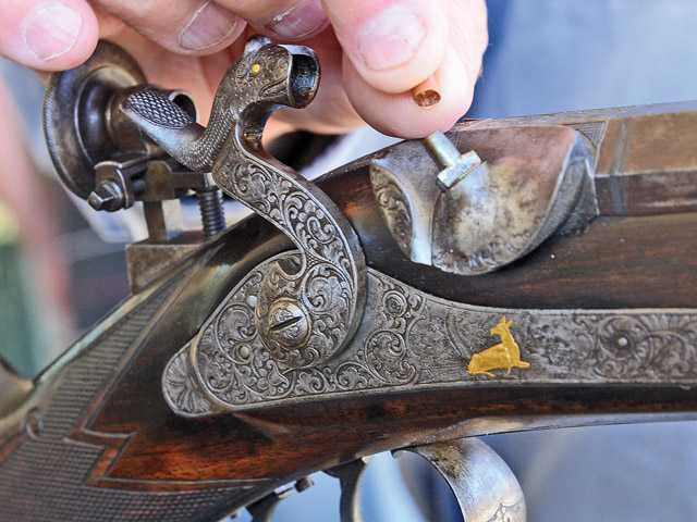 Burbank Muzzle Loaders president Tom Trevor places a cap on the lock of his rifle.