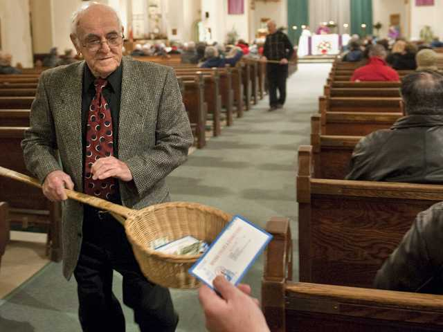 In this Saturday, Dec. 19, 2009 photo, John Alves, of Dartmouth, Mass., uses a basket while taking collection during Mass at St. John the Baptist Roman Catholic Church in New Bedford, Mass.
