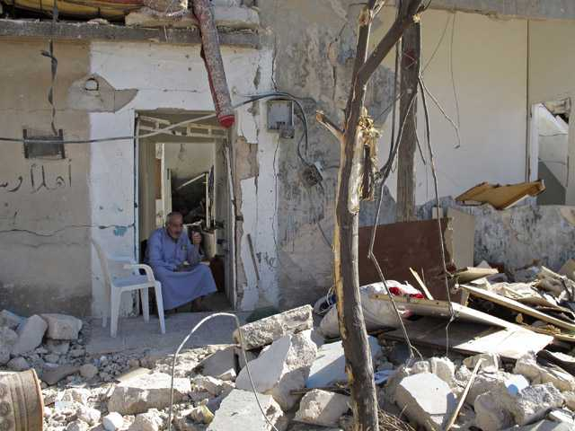 Syrian Mahmoud Jikar sits at the door of his house, which was destroyed in a Syrian government bombing last week that killed more than 40 people, in Azaz, Syria, on Monday.