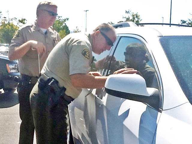 Deputies Tom Drake, left, and Mike Perry of the Santa Clarita Valley Sheriff's Station try to free a toddler from a locked  SUV at the Westfield Valencia Town Center on  Monday.