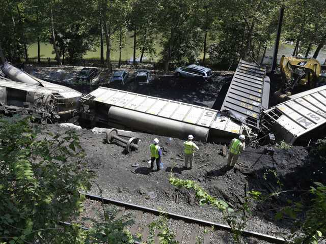 Officials inspect part of a CSX freight train that derailed alongside a parking lot overnight in Ellicott City, Md., Tuesday. Authorities say the train, hauling coal from West Virginia to Maryland, derailed and fell from a bridge near Baltimore, killing two college students who were on the tracks.