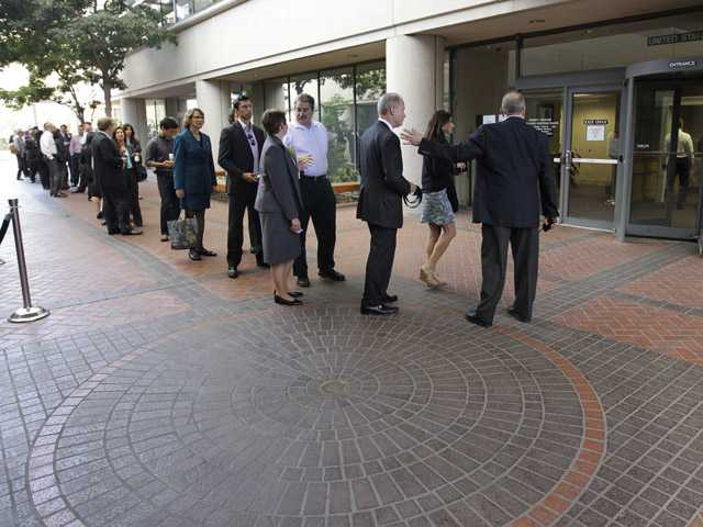 People wait in line to get inside for the Apple and Samsung trial during a lunch break at a federal courthouse in San Jose, on Tuesday.