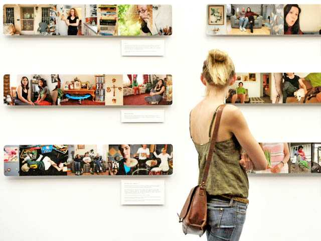 "Hannah Standerfer, 17, of Quartz Hill, looks at ""Avoca Street,"" a documentary project by Audrey Madelbaum, on display at the ""Big Big Backyard"" exhibit at the College of the Canyons art gallery in Valencia on Tuesday."