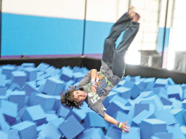 Justin Barragan, 11, dives into a foam-cube pit at Jump 5150, a new trampoline family recreation center, in Valencia on Saturday.