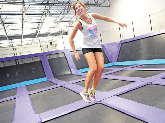 Party coordinator Sydney Thompson enjoys a moment on one of the wall-to-floor trampolines at Jump 5150, a new trampoline family recreation center, in Valencia on Saturday. The business will be open six days a week and closed Mondays.