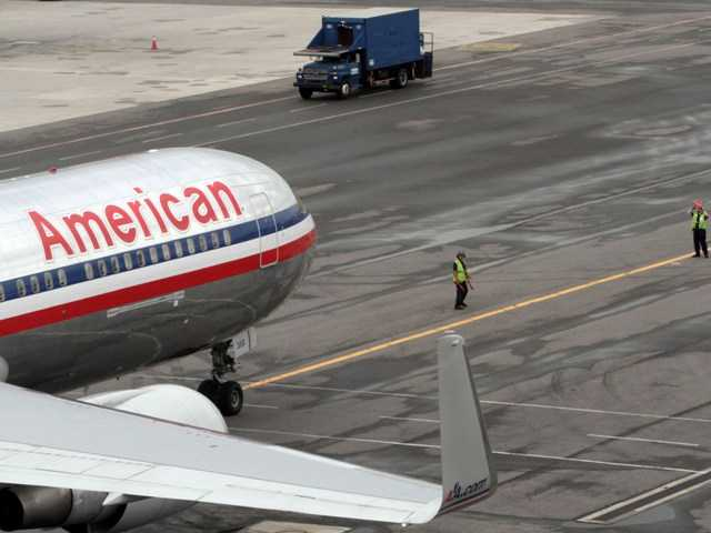 In this Wednesday, Aug. 1 2012 photo, American Airlines grounds crew assist the pilot as he pushes the airplane back from the gate at JFK International airport in New York.