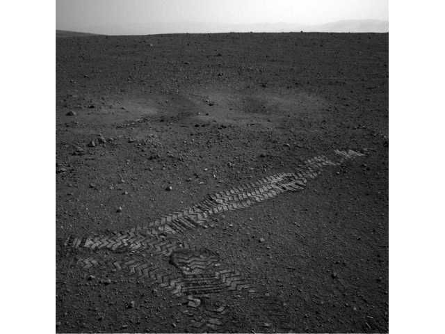 This image dated Wednesday Aug. 22, 2012 and provided by NASA shows the Curiosity rover's wheel tracks on the surface of Mars.