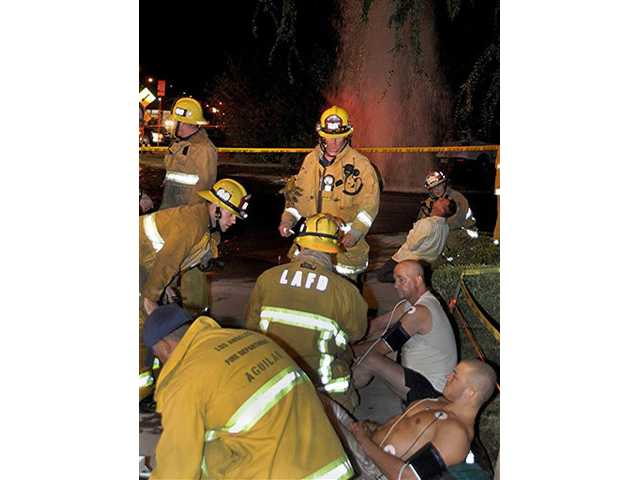 Firefighters and paramedics examine two of the eight patients who were shocked after attempting to aid a car crash victim as water gushes from hydrant in North Hollywood on Wednesday.