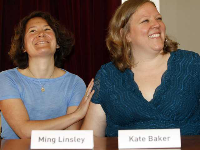 Ming Linsley, left, and Kate Baker smile during a news conference in Montpelier, Vt., on July 19, 2011. An agreement was reached Thursday, settling a lawsuit against the Wildflower Inn for refusing to host the lesbian couple's wedding reception.