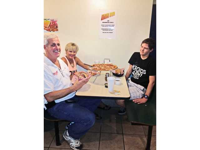 The Mills family, left to right, David, Debbie and Ryan, enjoy pastrami and pizza at Grinder's Deli.