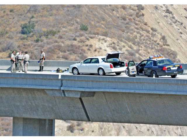 California Highway Patrol officers and Sheriff's deputies investigate an apparent suicide on the transition road from southbound Interstate 5 to northbound Highway 14 in the Newhall Pass on Thursday.