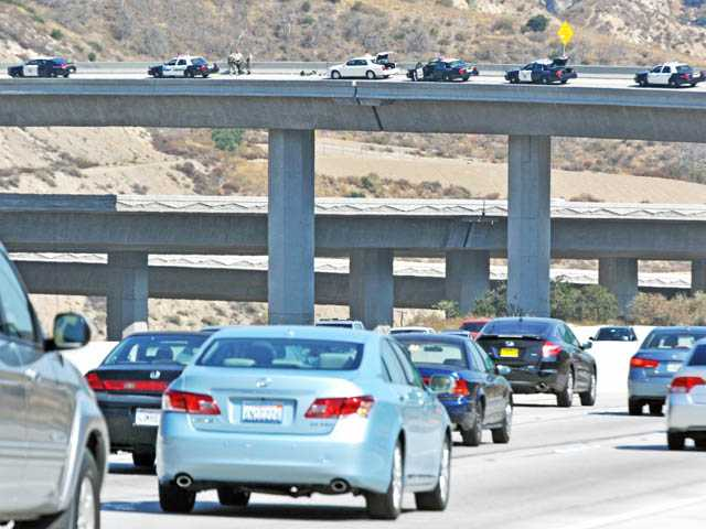 Traffic continues to flow on the southbound lanes of Interstate 5 as CHP officers and Sheriff's deputies investigate an apparent suicide on the transition road to Highway 14 in the Newhall Pass on Thursday.