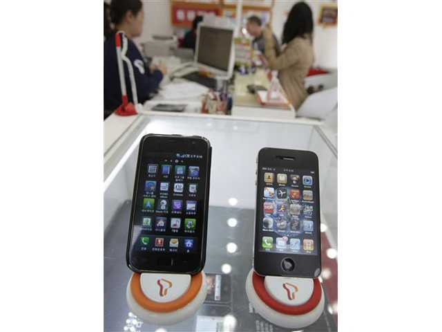 Samsung Electronics' Galaxy S, left, and Apple's iPhone 4 are displayed at a shop in Seoul, South Korea.