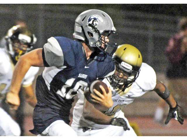 Saugus quarterback Chris Hamilton (10) runs against Calabasas on Thursday at COC.