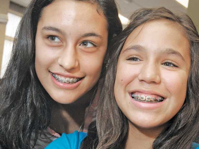 Belicia Cespedes, 15, left,  and sister Giana, 12, display their braces  during a visit to have their braces tightened at Valencia Children's Dental Group in Valencia on Aug. 16.