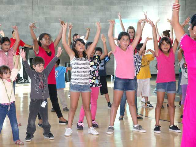 Children participate in an activity led by Blue13 Artistic and Executive Director Achinta S. McDaniel, right, at the Santa Clarita Community Center in Newhall on Thursday.