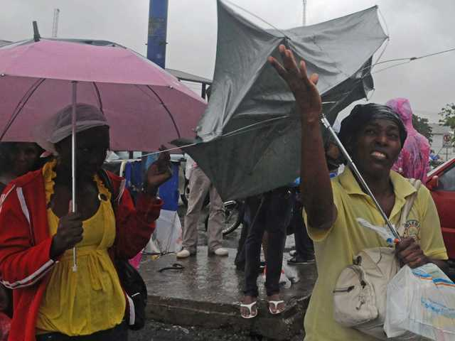 A woman struggles with her umbrella due to the wind as Tropical Storm Isaac affects Santo Domingo, Dominican Republic, Friday.