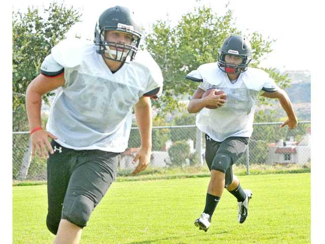 Santa Clarita Christian offensive lineman Danny Blake, left, and running back Derek Lewis practice on Aug. 17 at Canyon Country Park.