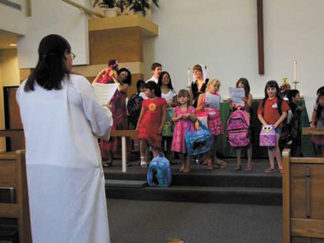 Children assembled on the altar with backpacks, receiving a blessing from Rev. Susan Bek.
