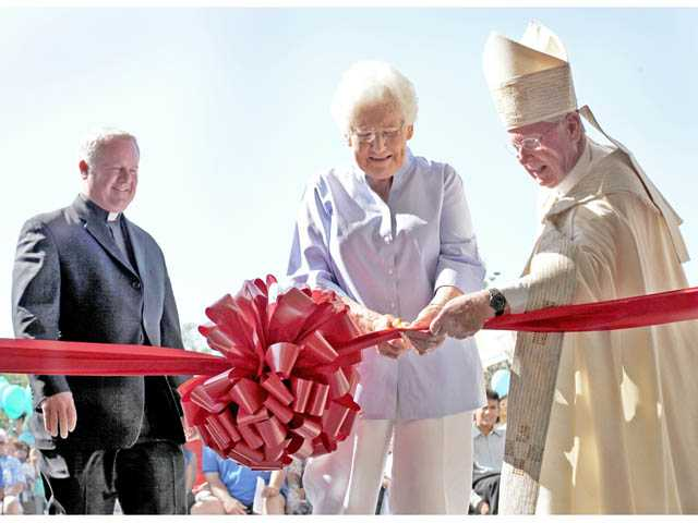 Our Lady of Perpetual Help Church member Joanne Redmond, center, Monsignor Richard Martini, left, and Bishop Gerald Wilkerson, right, cut the ribbon of the new pastoral center in Newhall on Friday.