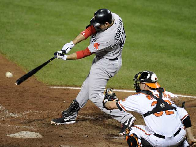 Boston Red Sox's Adrian Gonzalez, left, singles and drives in a run during a baseball game against the Baltimore Orioles on Thursday.