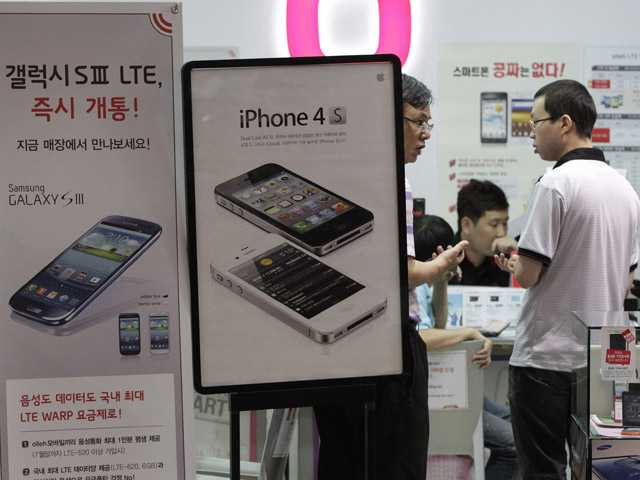 Banners advertising Samsung Electronics' Galaxy S III, left, and Apple's iPhone 4S are displayed at a mobile phone shop in Seoul, South Korea, on Friday.