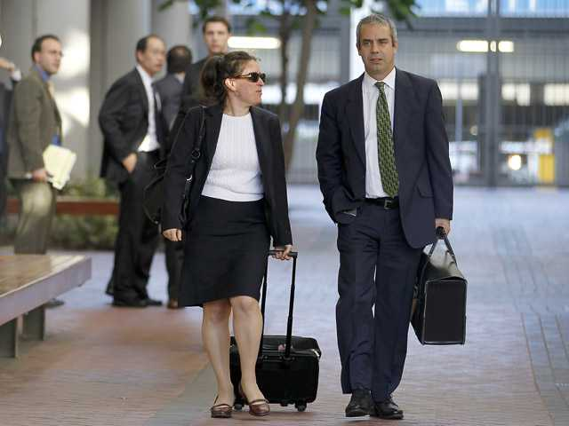 Kevin Johnson, right, and Victoria Maroulis, left, attorneys for Samsung, leave the US Courthouse and Federal building after a jury reached a decision in the Apple Samsung trial on Friday in San Jose.