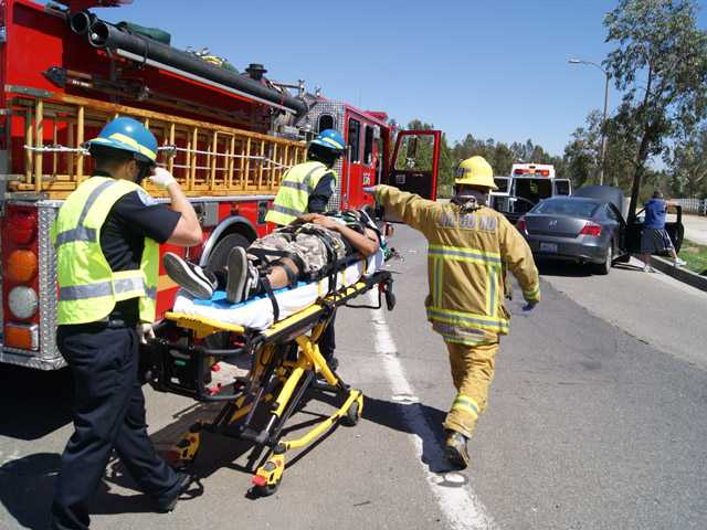 Paramedics cart a man to an ambulance after a collision in Valencia on Sunday.