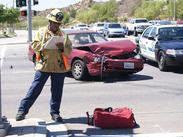 A firefighter takes notes at the intersection of Copper Hill Drive and Newhall Ranch Road, where a collision occured Sunday.