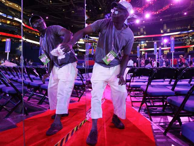 Worker Patrick Gayle wipes the mirror-sided camera stands on the floor of the Republican National Convention in the Tampa Bay Times Forum.