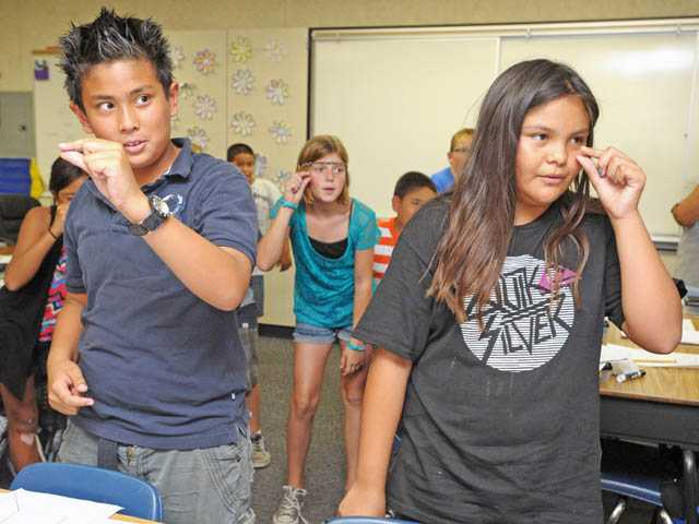 "Fifth-graders Benicio Preciado, 9, left, and Anahi Martinez, 10, making a gesture representing the word ""minute"" as their class studies homographs at Rio Vista Elementary School in Canyon Country on Wednesday."