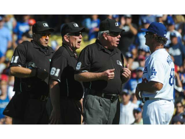 Umpires confer with Los Angeles Dodgers manager Don Mattingly during a game against the Miami Marlins on Sunday in Los Angeles.