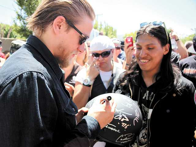 """Anthony Munoz, 23, right, gets an autograph from actor Charlie Hunnam, left, of """"Sons of Anarchy"""" at The Boot Ride on Sunday in Canyon Country."""