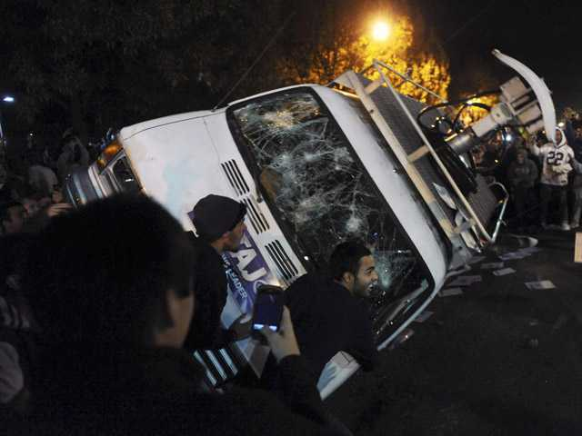 In this Nov. 10, 2011 file photo, Penn State students flip a television news van during a riot off campus in State College, Pa., after the Penn State board of trustees fired football coach Joe Paterno.