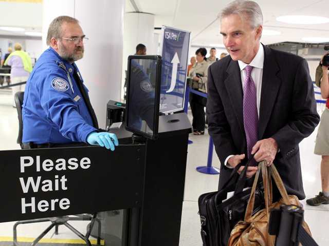 TSA screened a passenger to board his American Airlines flight at Lambert-St. Louis International Airport July 31. The FAA is studying allowing people to use electronic devices during flights.