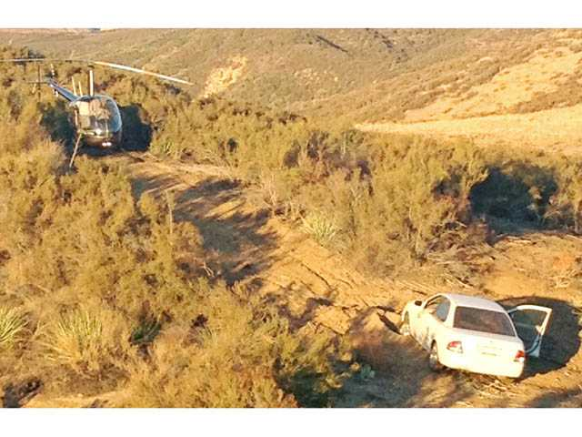 A helicopter piloted by Jason Hassler lands near the stranded Richard and Joyce Larson on Monday in Castaic.