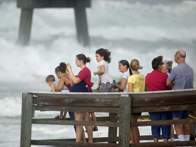 A crowd gathers on the end of the boardwalk on Okaloosa Island in Fort Walton Beach, Fla., to watch rough surf generated by Hurricane Isaac.