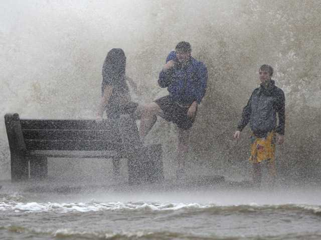 People walk in the storm surge from Isaac, on Lakeshore Drive along Lake Pontchartrain, as the storm approaches landfall, in New Orleans, on Tuesday.