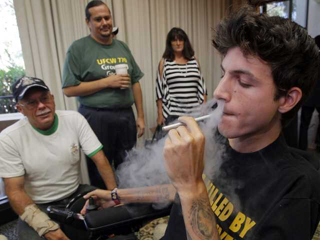 Michael Oliveri, right, medical cannabis patient, smokes marijuana during a news conference in Universal City on Wednesday.