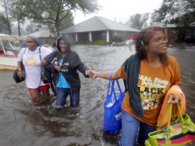 St. John the Baptist Parish sheriff's deputies evacuate residents from the River Forest subdivision in LaPlace, La. as wind-driven tides flood the neighborhood Wednesday, Aug. 29, 2012.