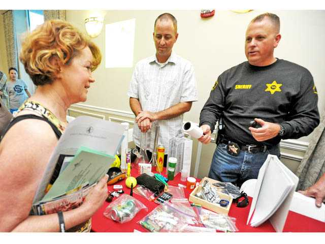 "Det. Bill Velek, center, and Dep. Joe Crilly, right, of the Santa Clarita Valley Sheriff's Station's Juvenile Intervention Team demonstrate how drugs can be hidden in ordinary household items, including a lint remover roller, as Marla Mosco, left, listens  during the ""Heroin Kills: One Year Later"" symposium at the Santa Clarita Activities Center on Wednesday."