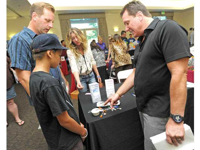 "Janete Stamboulian, center, and Scott Andrew, right, a counselor and life coach, describe drug paraphernalia to Paul Broz, left, and Vincent Broz, 11, at the ""Heroin Kills: One Year Later"" symposium at the Santa Clarita Activities Center on Wednesday"